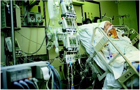 This man is recovering from quadruple bypass surgery in an intensive care unit. (Custom Medical Stock Photo. Reproduced by permission.)