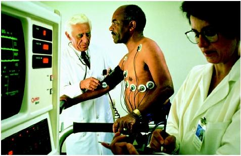 Doctors monitor a patient's vital signs during a stress test. (Photograph by Mug Shots. The Stock Market. Reproduced by  permission.)